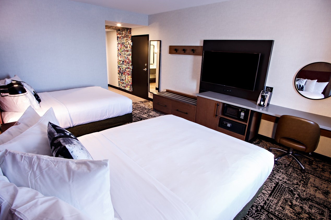 Double queen bedroom showing bed with white sheets, desk to work and a large television