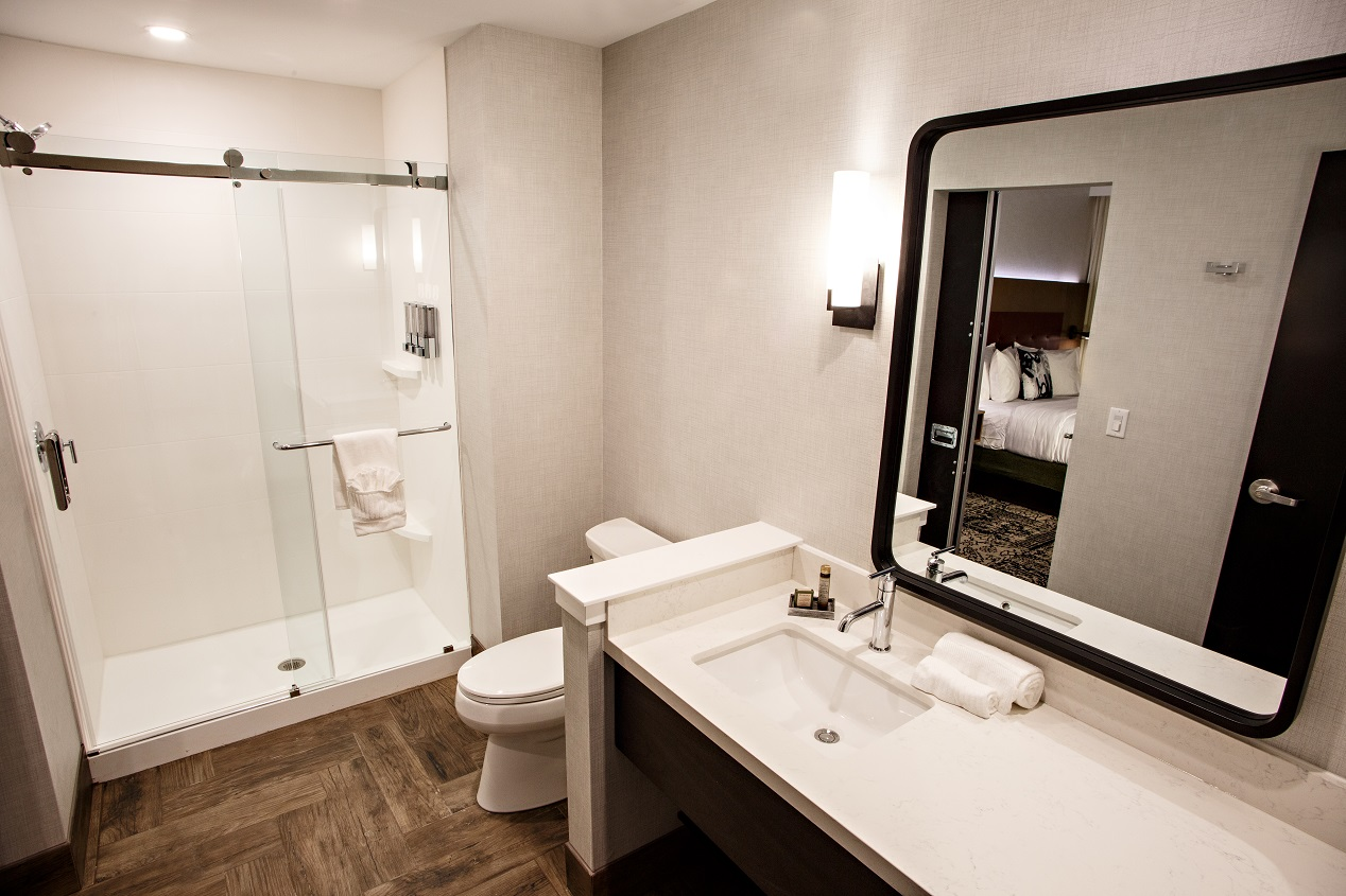 Hotel Rock Lititz bathroom showing white countertops, toilet and standing shower