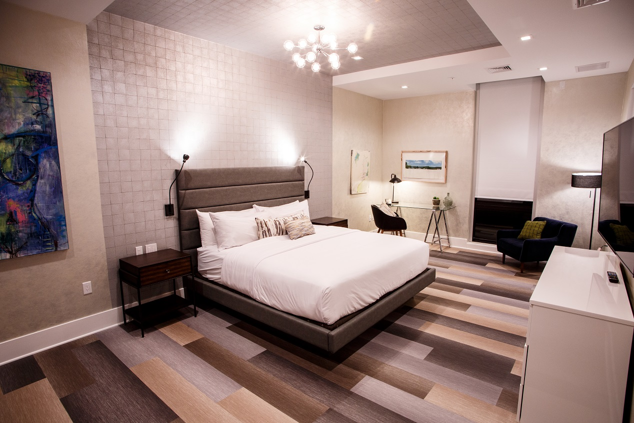 Bedroom in a penthouse suite with a white large bed, desk for work, loveseat and television