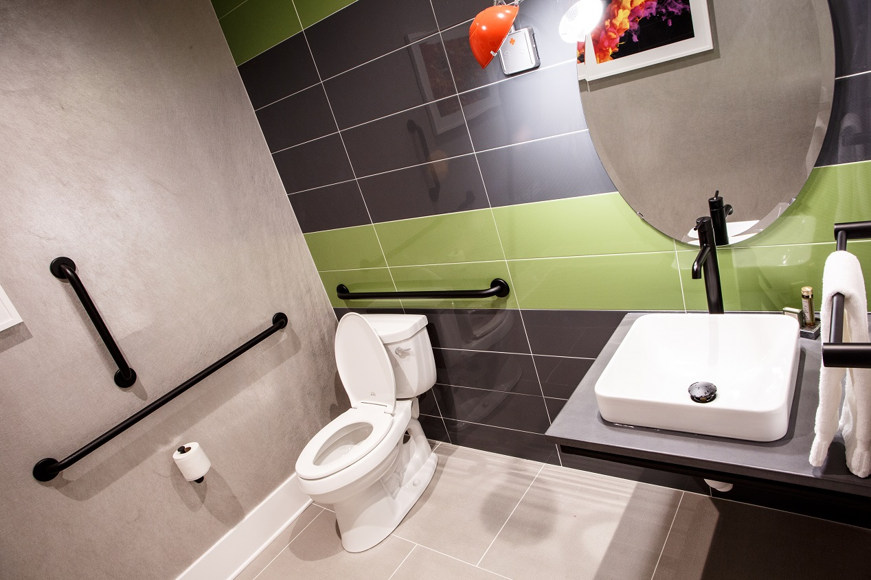 Penthouse suite bathroom showing toilet and sink with green and gray tiling